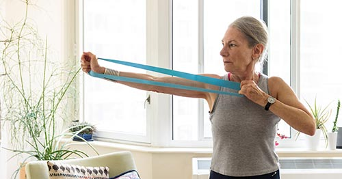 A woman using a stretch band to strengthen her elbow.