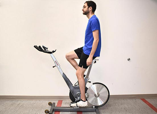 man on exercise bike demonstrating seat height position