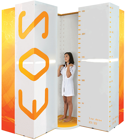 Photo of an EOS imaging cabin kiosk with an adolescent girl standing inside.