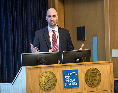 Image: Jonathan Avery, MD, speaking at a podium at HSS.