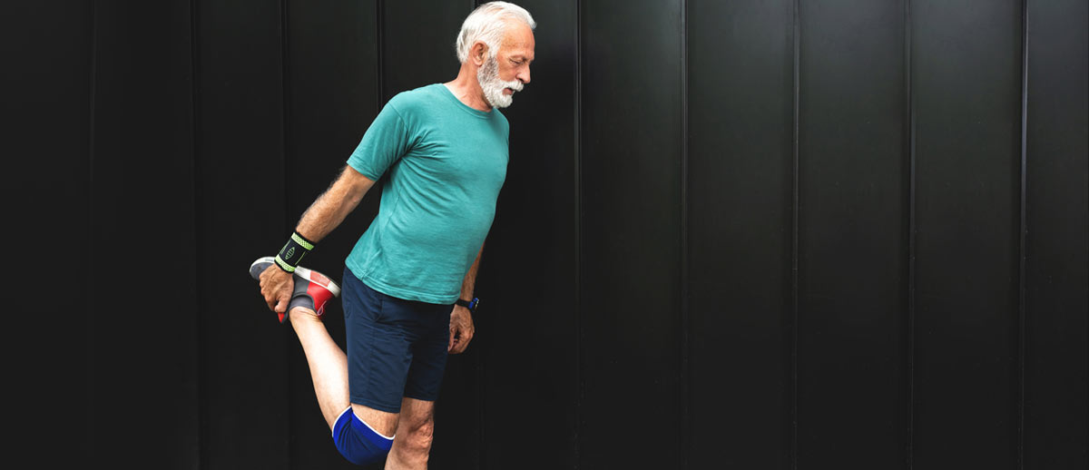 photo of older man stretching leg before workout