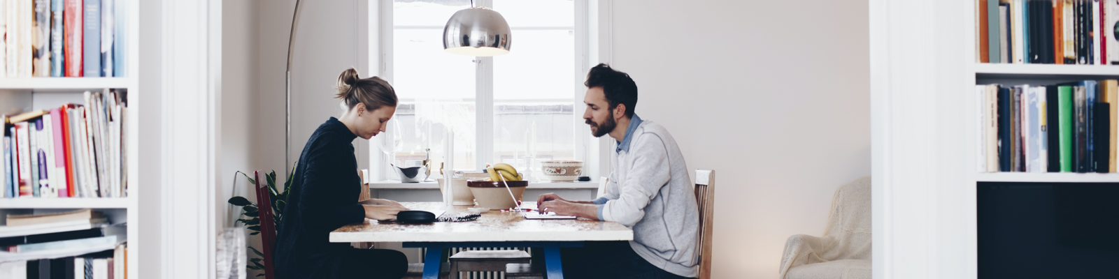Banner image of a man and woman siting at a shared desk, face to face, working on their laptops.