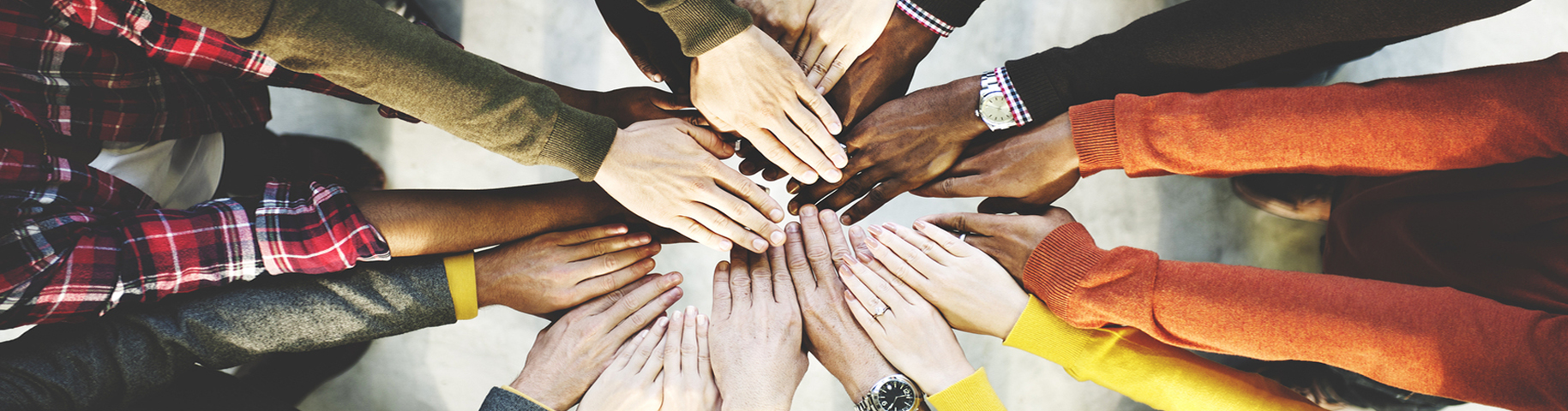 Banner image of the hands of many different people all together in the center of a circle.