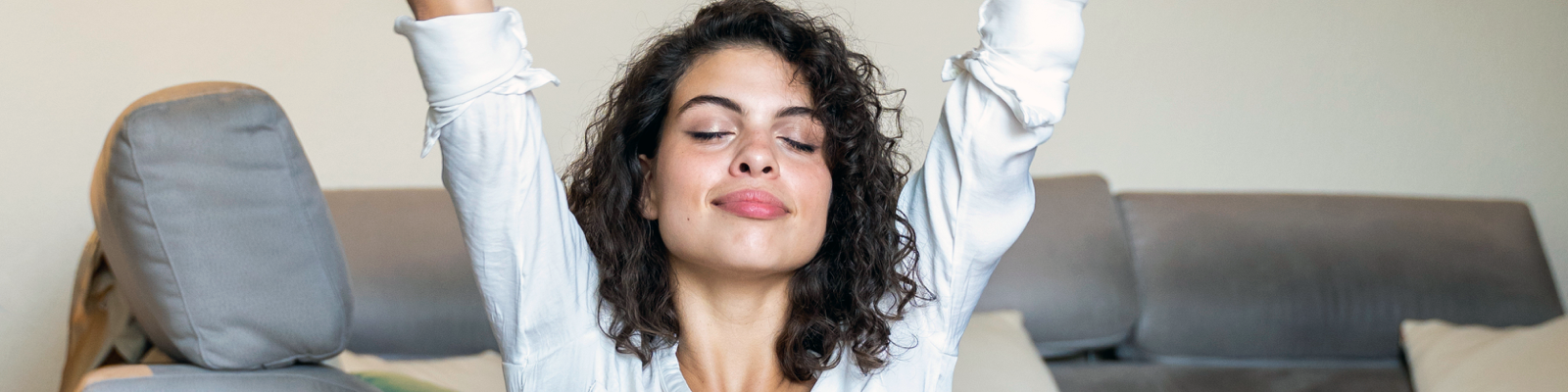 Banner image of a woman smiling with her eyes closed and her arms raised as if she is stretching.