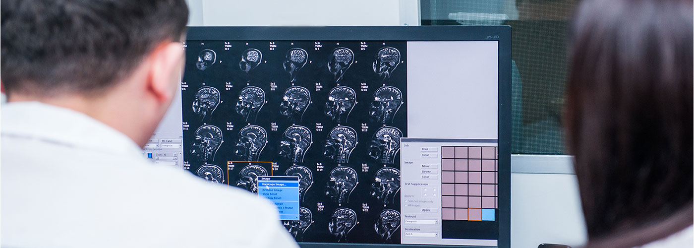 Banner image of a physician reviewing image scans.