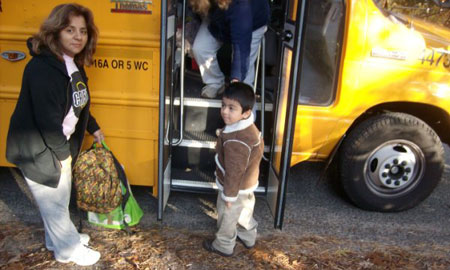 Photo of Ismael Vega and his mom as Ismael boards the bus
