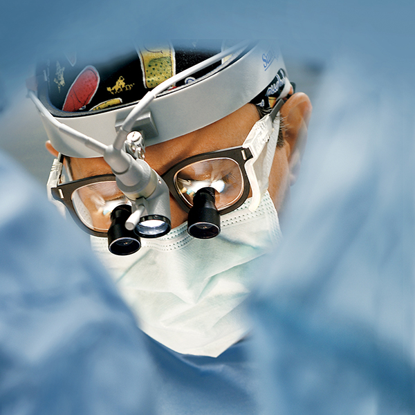 Image - surgeon using magnifying lenses