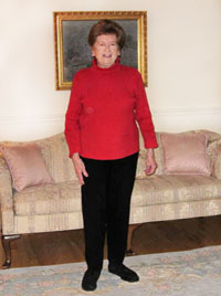 Photo of Joan Campbell standing in her living room.