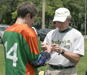 Photo of John Cavanaugh examining a lacrosse player