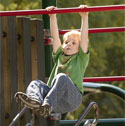 Photo of a child hanging from monkey bars at the park