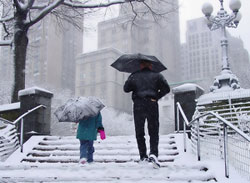 Photo of a parent and child walking on a snowy day.