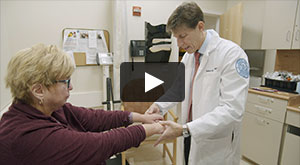 Video thumbnail image of Dr. Robert Spiera examining a female patient's hands.