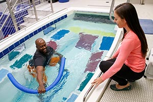 Photo of a man in a pool working with a physical therapist
