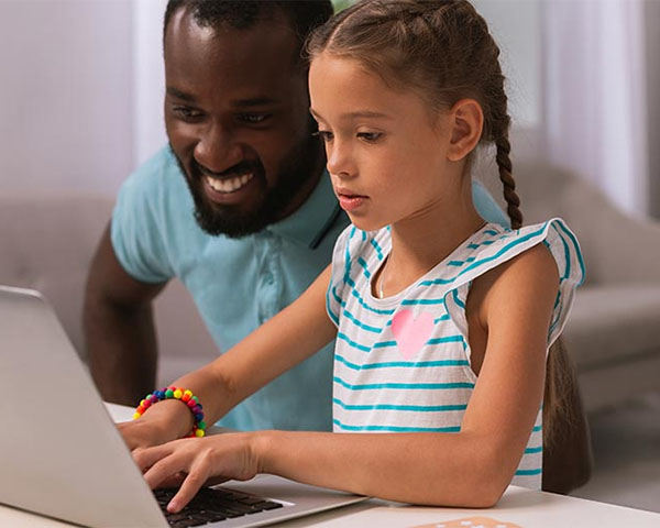 photo of young father and daughter using laptop