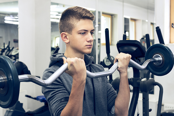 teenager lifting weights at the gym