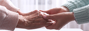 Photo of a person's hands grasping those of a caregiver.