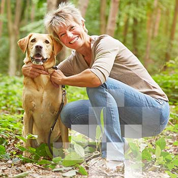 Image - a woman kneeling down and petting a dog