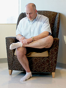 Photo of a man crossing his ankle over his knee to put on his sock.