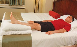 image of man laying in bed with left leg propped on pillows