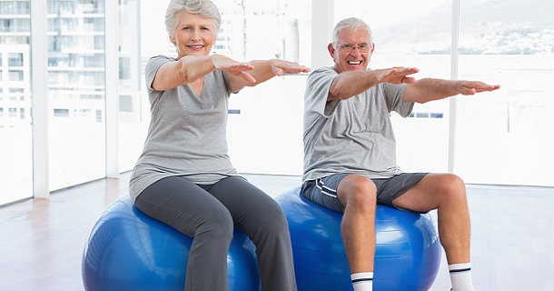 Happy senior couple doing stretching exercises on fitness balls