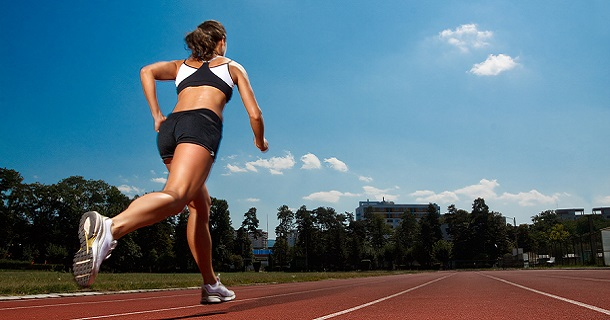 Woman running on track field