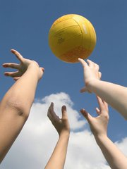 Hands reaching for volleyball