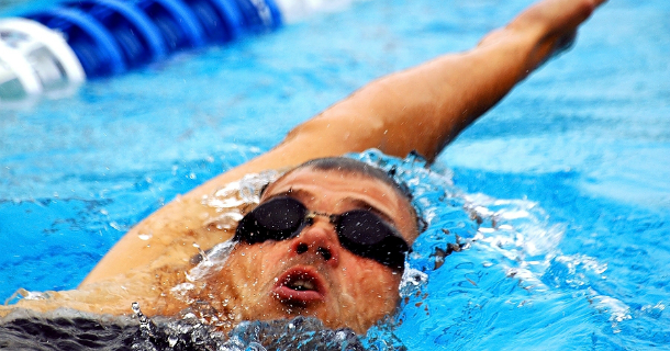 Swimmer doing backstroke in pool