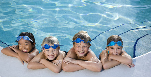 Children Smiling at the Edge of a Swimming Pool