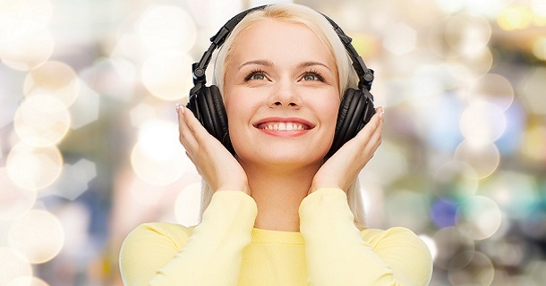 music and technology concept - smiling young woman listening to