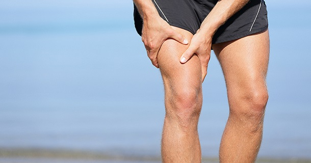 Muscle injury. Man with sprain thigh muscles. Athlete in sports shorts clutching his thigh muscles after pulling or straining them while jogging on the beach.