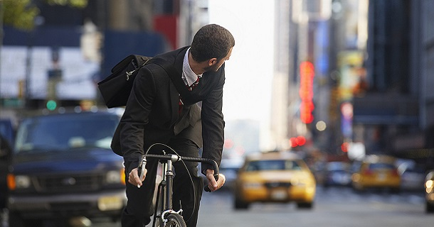 Young businessman looking over shoulder while riding bicycle on