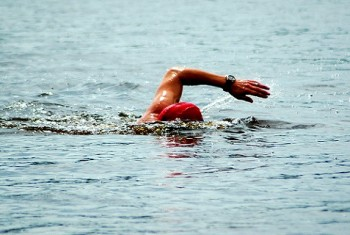A white arm of a caucasian swimmer athlete swimming in the lake