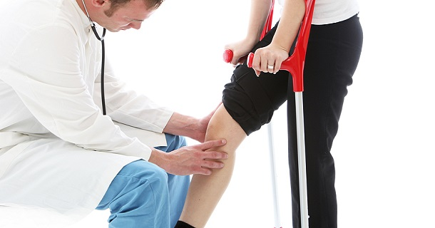 Physician examining knee of person standing on crutches