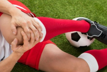 Soccer Player holding knee in pain