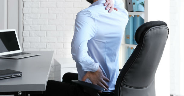 man sitting at office desk with back pain