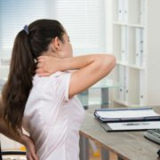 woman experiencing back pain at work