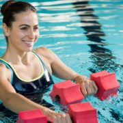 Fit woman working out with foam dumbbells in swimming pool