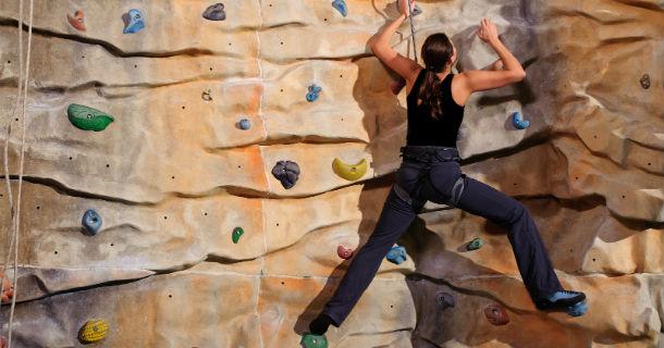 Woman Climbing Rock Wall