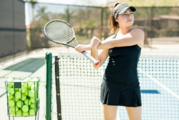 Young woman warming up on tennis court