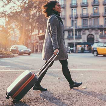 Image - woman walking on a city street pulling a suitcase behind her