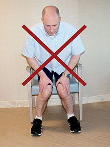 Photo showing the incorrect way to rise from a chair.