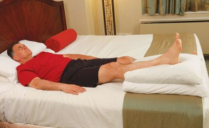 image of man laying in bed with right leg propped on pillows