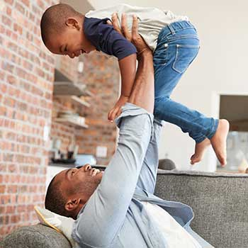 Image - man lifting young son into the air