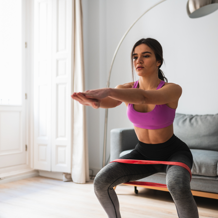 Image of a woman working out at home with a resistance band.